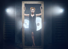 A woman in a dress posing near a frame Royalty Free Stock Photography