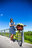 Woman in dress posing and vintage bicycle with wicker basket in Stock Image