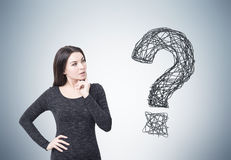 Woman in dress and question mark on gray wall Royalty Free Stock Photos