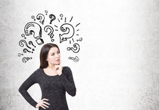 Woman in dress and question marks on concrete Royalty Free Stock Image