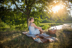 Woman in dress relaxing on blanket under tree and looking at sun. Beautiful woman in dress relaxing on blanket under tree and looking at sunset Royalty Free Stock Photography