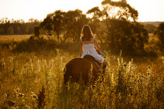 Woman in a dress riding on an adult horse Stock Photo