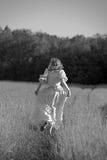 A woman in a dress runs away Royalty Free Stock Photos