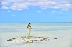 Woman in dress  on a sandbank in the ocean. Adorable young girl on sandy beach .  Young lady posing on beach. Outdoor relax leisure concept. Cuba. Caya Coco Royalty Free Stock Image
