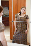 Woman in dress standing against mirror. Portrait of young Caucasian female in dress standing against mirror and looking at herself in domestic room Stock Images