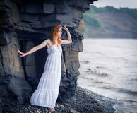 Woman in dress standing on beach. Redhead woman in dress standing on beach and looking to somewhere. Color toned image Royalty Free Stock Photography