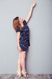 Woman in dress stretching hand up Royalty Free Stock Image