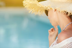 Woman  in a  dress and sunhat sits next a resort pool. Beautiful girl in a  dress and sunhat sits next a resort pool Stock Images