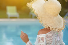 Woman  in a  dress and sunhat sits next a resort pool. Beautiful girl in a  dress and sunhat sits next a resort pool Royalty Free Stock Photography