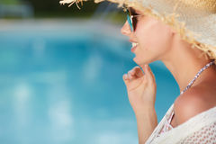 Woman  in a  dress and sunhat sits next a resort pool Royalty Free Stock Photography