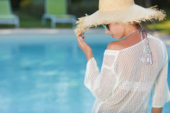 Woman  in a  dress and sunhat sits next a resort pool Stock Images