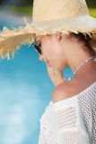 Woman  in a  dress and sunhat sits next a resort pool Royalty Free Stock Images