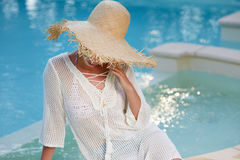Woman  in a  dress and sunhat sits next a resort pool Royalty Free Stock Photos