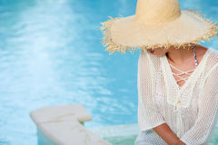Woman  in a  dress and sunhat sits next a resort pool Stock Photo