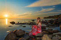 Woman in dress and sunset on a sea Stock Images