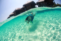 Woman in a dress swimmer in the ocean diving Stock Image