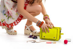 Woman in dress touches bag. Lipstick near lime purse. Bijouterie and cosmetics. Brand new accessories stock image
