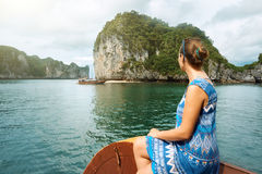 Woman in dress is traveling by boat among the islands in Halong. Attractive woman in a dress is traveling by boat in Halong Bay. Vietnam. Travel to Asia stock images