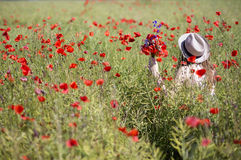 Woman  at dress walk in poppy field Royalty Free Stock Image