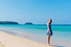 Woman in dress walking on beach Stock Image