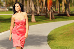 Woman in a dress walking in the park Royalty Free Stock Photos