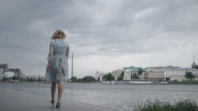 Woman in dress walking on seafront stock footage