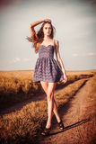 Woman in dress walking on the trail atl field Royalty Free Stock Photography