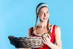 Woman in dress wearing wicker basket Stock Photo