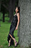 Woman with dress in wood. Attractive young woman with long black formal dress leaning against tree in countryside Stock Photo