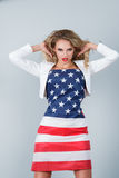 Woman dressed in american flag. Young expressive blonde woman wrapped in american flag against studio background Royalty Free Stock Photo