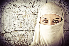 Woman dressed in Arab costume. Rusty wall in the background Royalty Free Stock Image