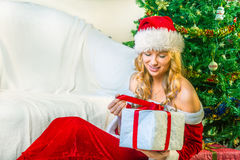 Woman dressed as Santa Claus opened a gift Stock Photography
