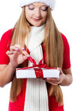 Woman dressed as Santa and opening xmas gift Royalty Free Stock Photos