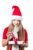 Woman dressed as Santa and opening xmas gift Royalty Free Stock Images