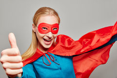 Woman dressed as a superhero with her thumb up Stock Images