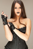 Woman dressed in balck. Young attractive woman dressed in black corset and gloves Stock Images