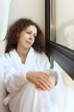 Woman dressed in bathrobe sits on windowsill Stock Photography
