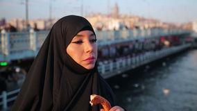 Woman dressed with black headscarf, chador eating, istanbul city. Woman dressed with black headscarf, chador eating simit, turkish bagel with istanbul city view stock video