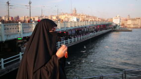 Woman dressed with black headscarf, chador eating, istanbul city stock video