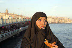 Woman dressed black headscarf, chador eating simit, istanbul, turkey Stock Images