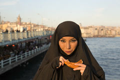 Woman dressed black headscarf, chador eating simit, istanbul, turkey Stock Photography