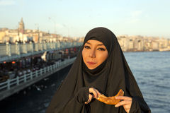 Woman dressed black headscarf, chador eating simit, istanbul, turkey Royalty Free Stock Images
