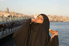 Woman dressed black headscarf, chador eating simit, istanbul, turkey Stock Photo