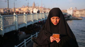 Woman dressed with black headscarf, chador using mobile phone stock video