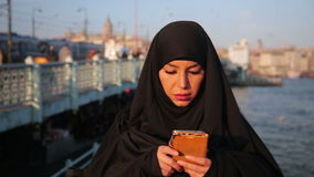 Woman dressed with black headscarf, chador using mobile phone stock footage