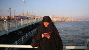 Woman dressed with black headscarf, chador using mobile phone, istanbul stock video footage