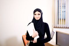 Woman dressed in black and wearing the hijab while working in the office Stock Image