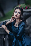 Woman in blue near old building. Woman dressed in blue victorian dress stand near old building Stock Photos