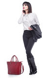 Woman dressed in business attire with a red bag. Young woman dressed in business attire with a red bag Royalty Free Stock Photos