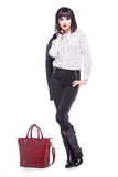 Woman dressed in business attire with a red bag. Young woman dressed in business attire with a red bag Stock Photos